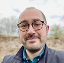 Zarino Zappia, wearing thick black and tortoise-shell glasses, a check shirt and a tweed Ted Baker jacket