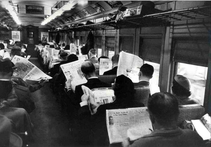 A mid-20th century train carriage full of passengers reading news papers