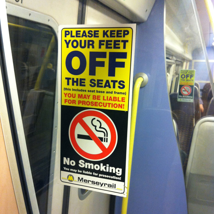 A Merseyrail sign warning customers to keep their feet off seats and refrain from smoking